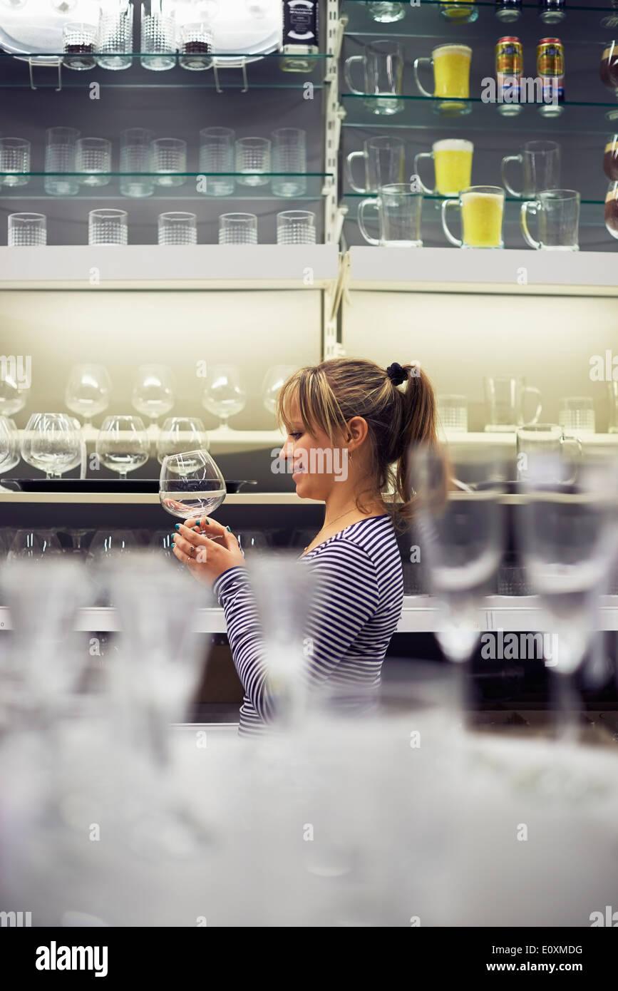Giovane donna ispanica shopping per mobili, bicchieri, piatti e home decor in negozio Immagini Stock