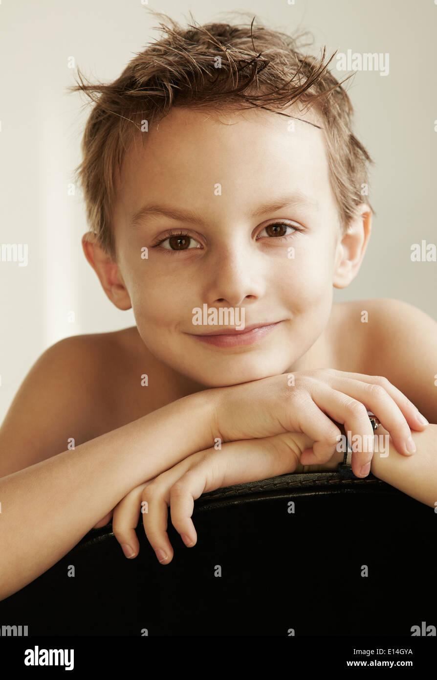 Ritratto di un 7-8 anni vecchio ragazzo appoggiandosi con le mani e la testa sul retro di una sedia Immagini Stock