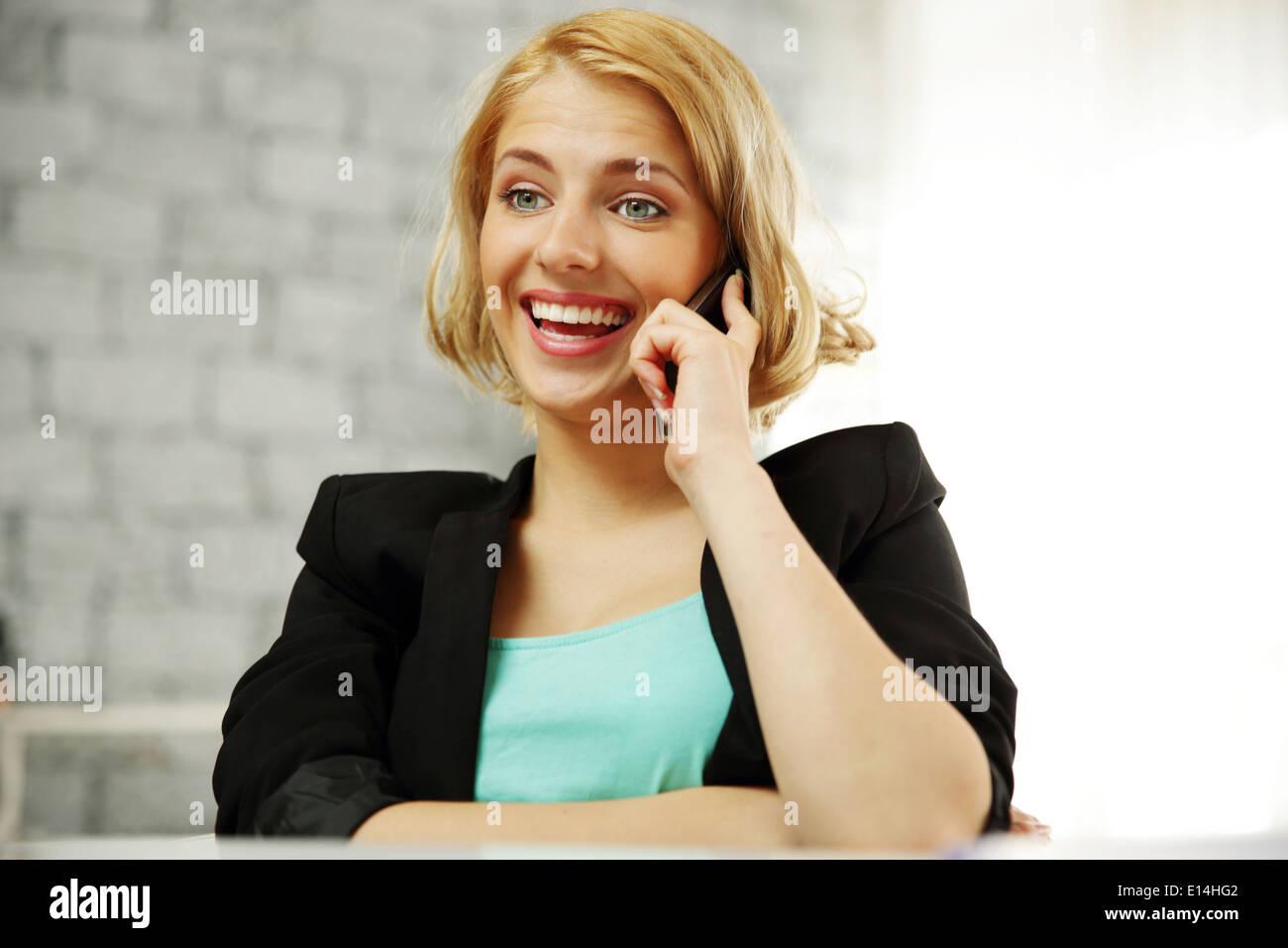 Ridendo giovane donna parlando in ufficio in ufficio Immagini Stock