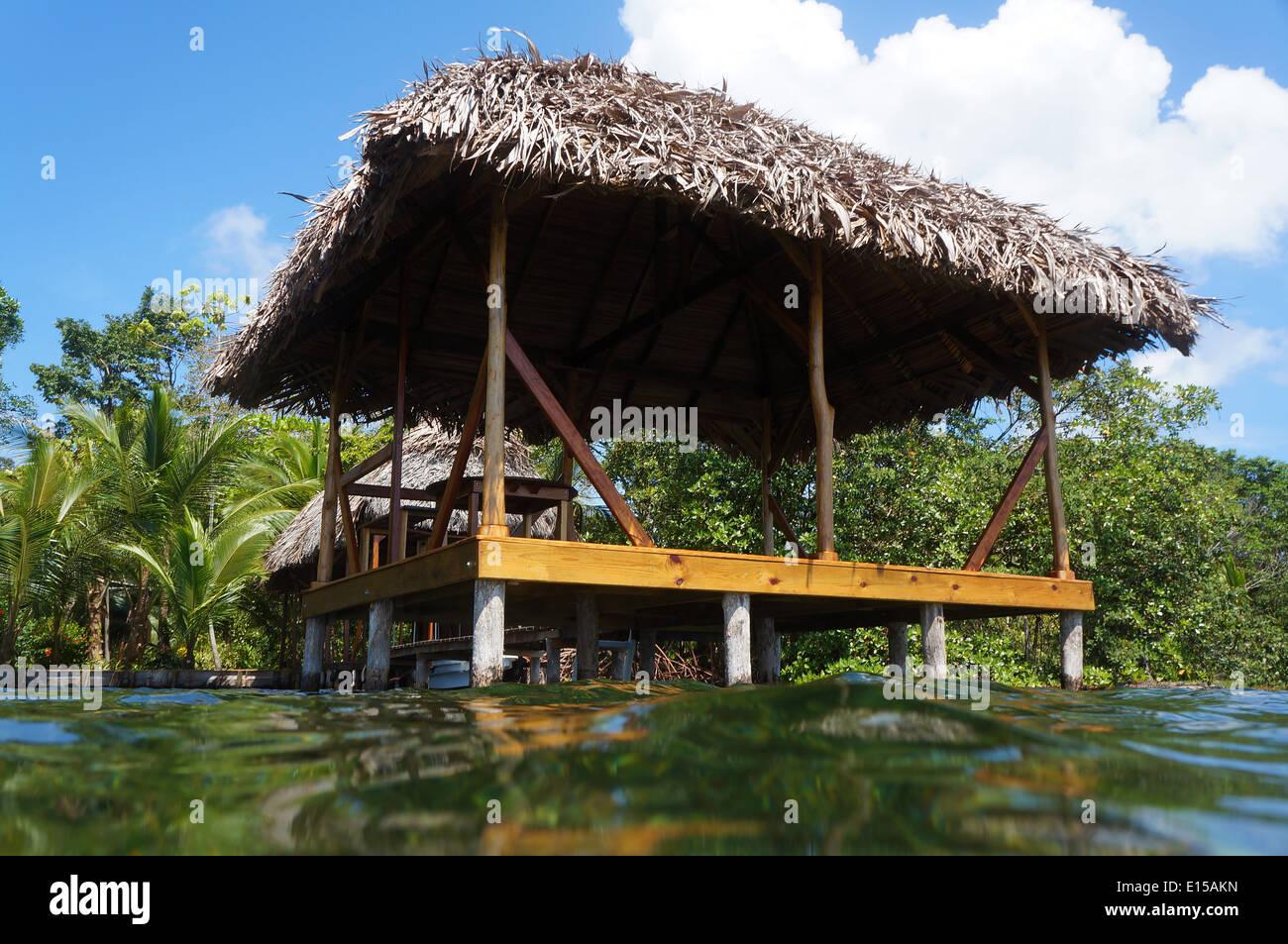 Capanna con il tetto di paglia su palafitte visto dalla superficie del mare Immagini Stock