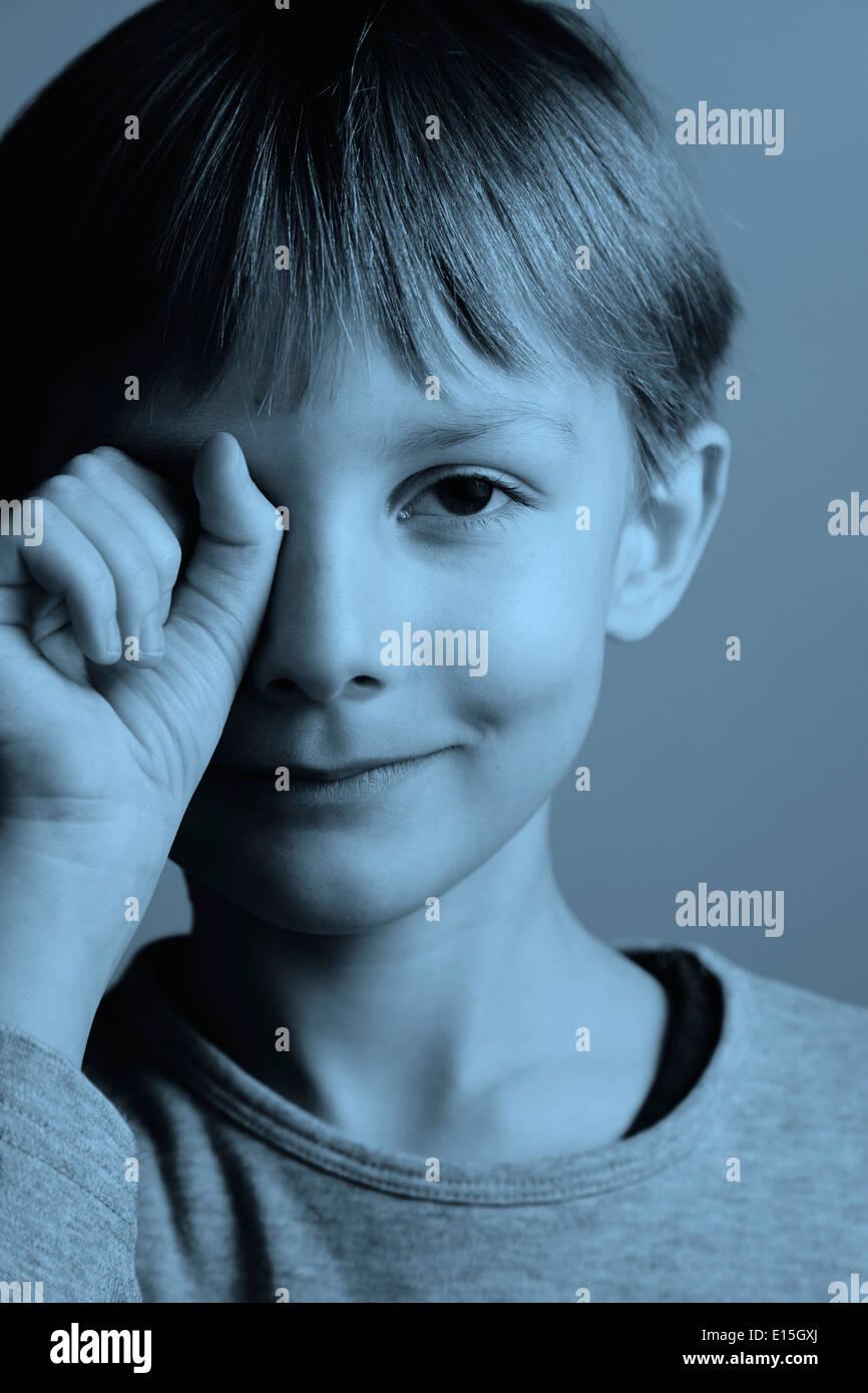 Un ragazzo 7-8 anni tenendo una mano davanti al suo occhio Immagini Stock