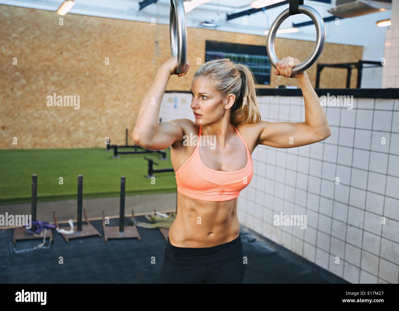 Montare la giovane donna di contenimento degli anelli ginnasta presso la palestra guardando lontano. Giovane donna caucasica esercizi in palestra. Immagini Stock