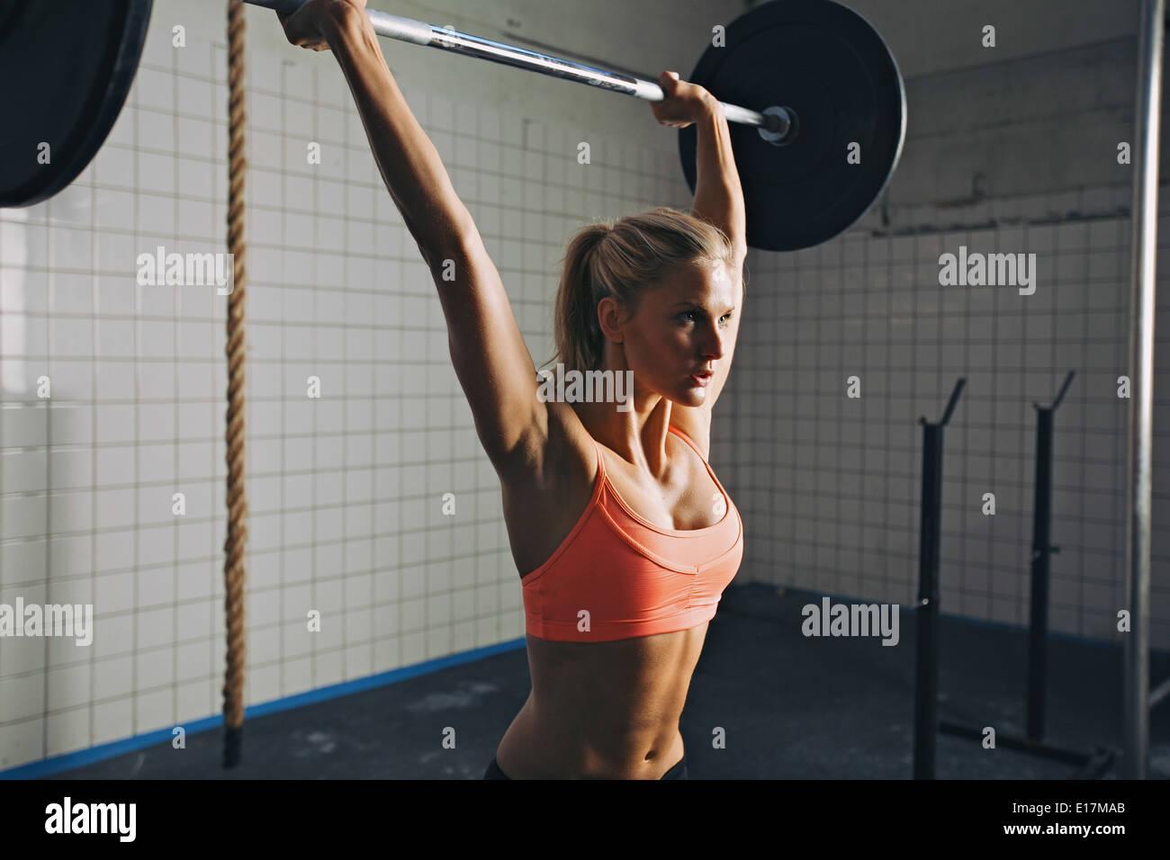 Donna forte sollevamento barbell come una parte di crossfit esercizio di routine. Montare la giovane donna di sollevamento pesi pesanti in palestra. Immagini Stock