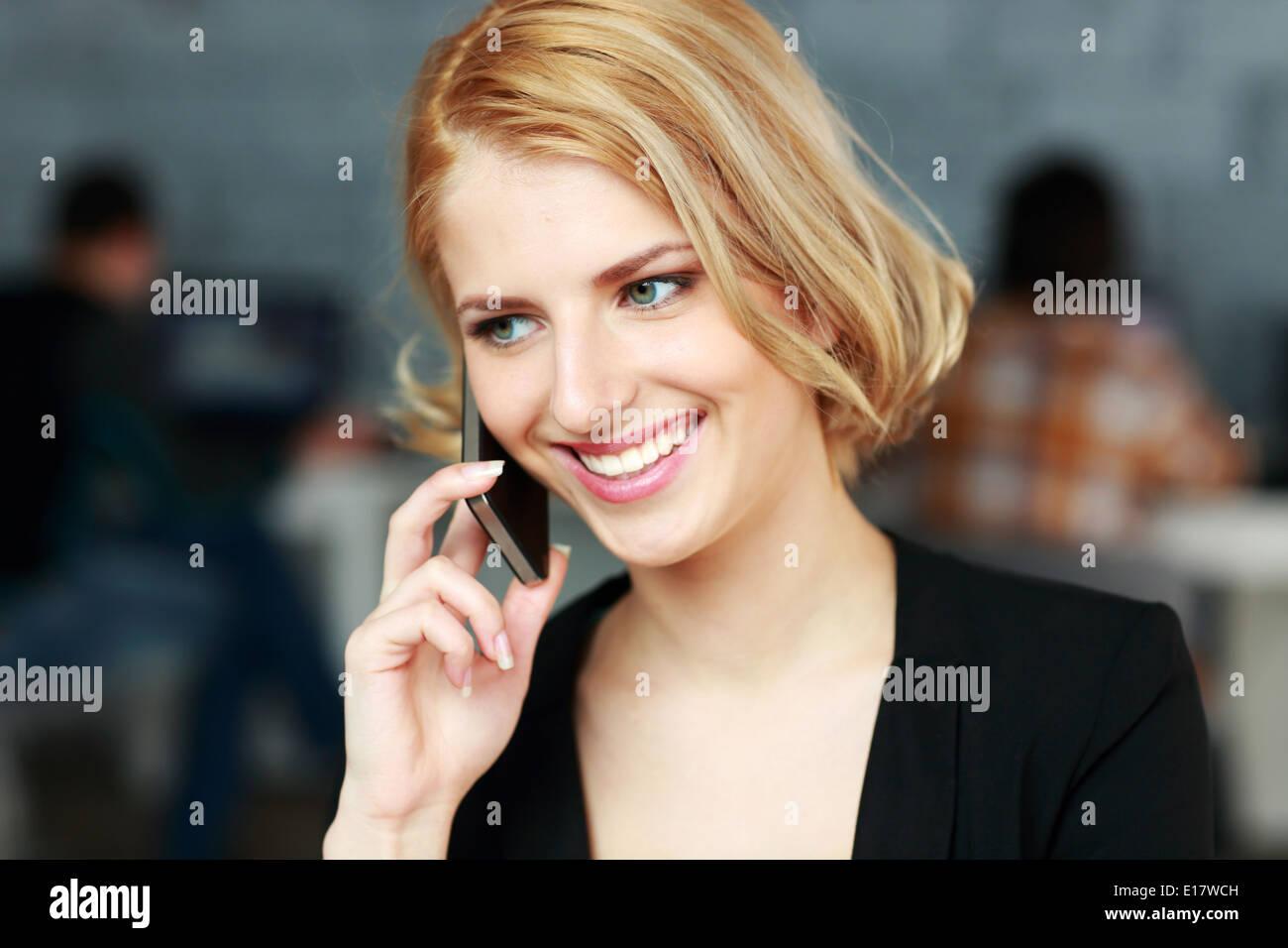 Allegro bionda imprenditrice parlando al telefono in ufficio Immagini Stock