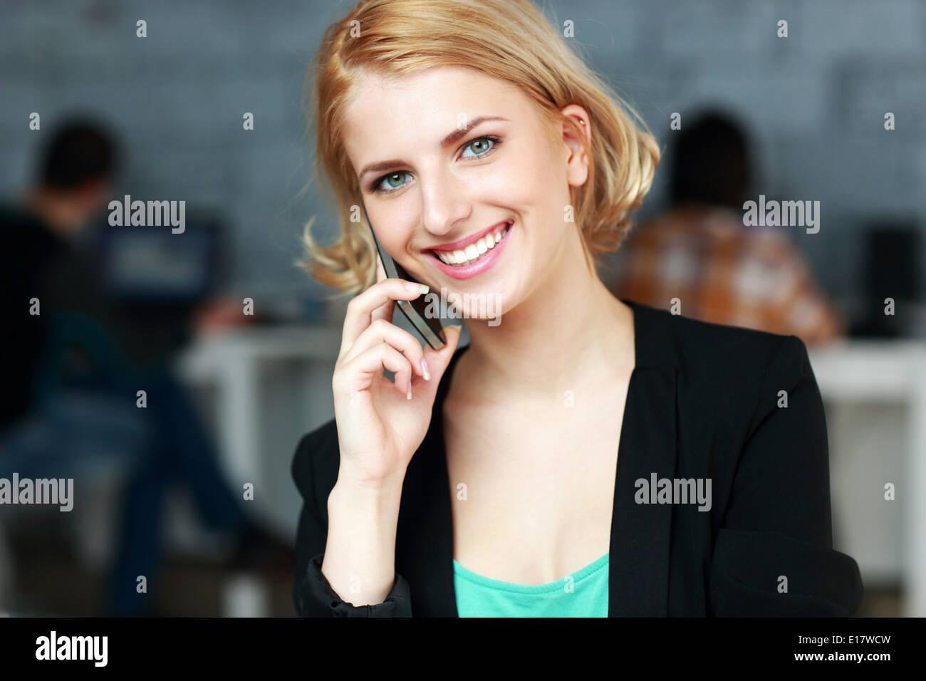 Felice imprenditrice parlando al telefono in ufficio Immagini Stock