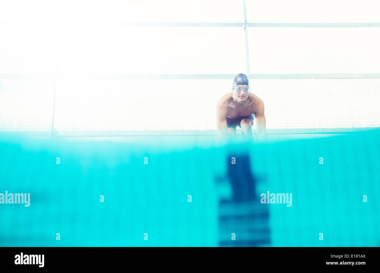 Nuotatori in bilico su blocchi di partenza Immagini Stock