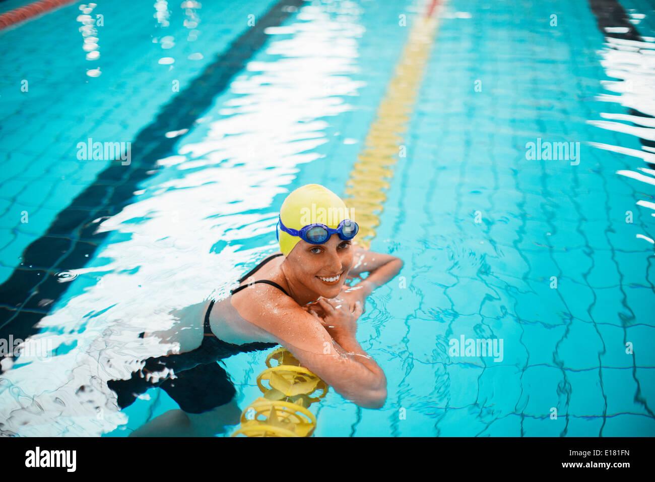 Ritratto di sorridere nuotatore appoggiandosi a nuoto il marcatore di corsia in piscina Immagini Stock