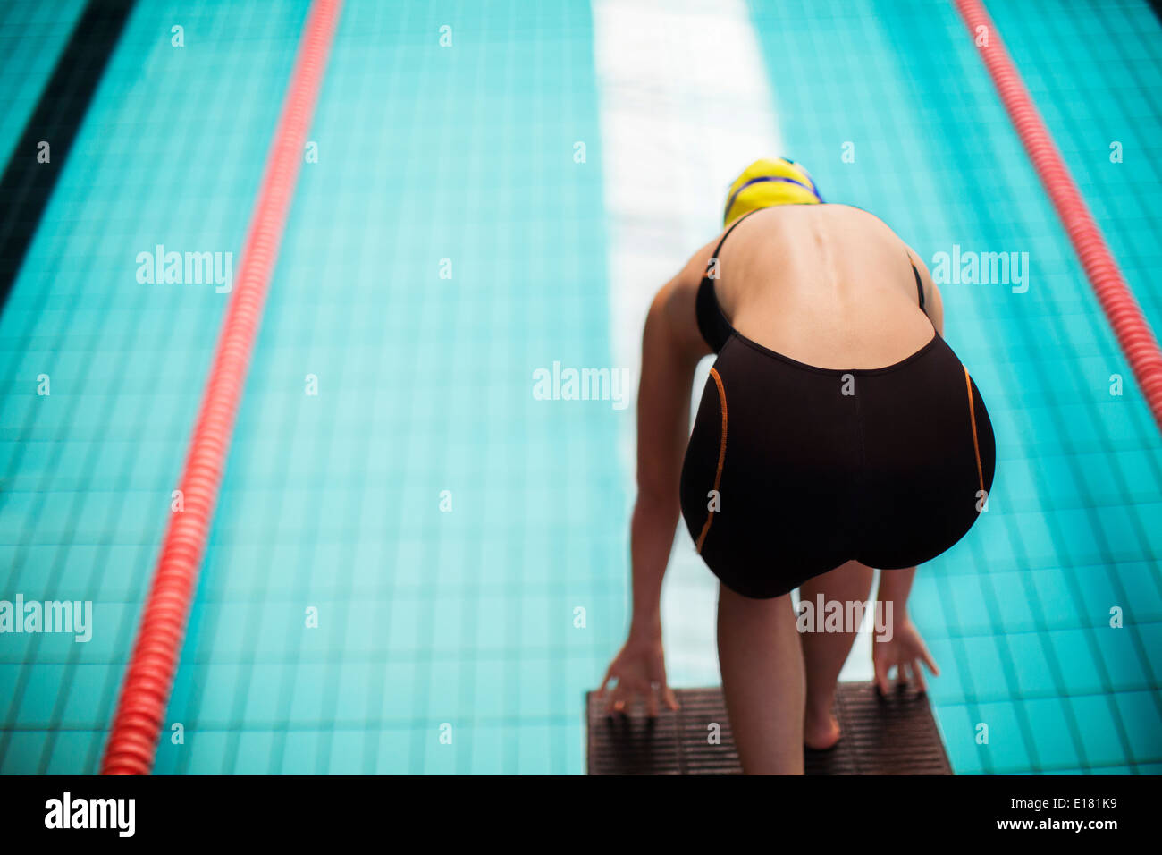 Nuotatore in bilico nel blocco di partenza sopra la piscina Immagini Stock