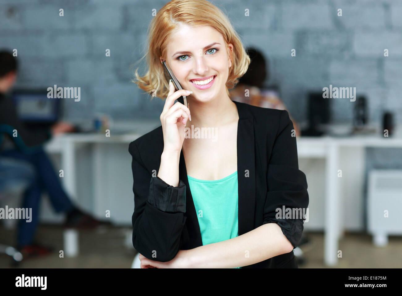 Giovane imprenditrice sorridente parlando al telefono in ufficio Foto Stock
