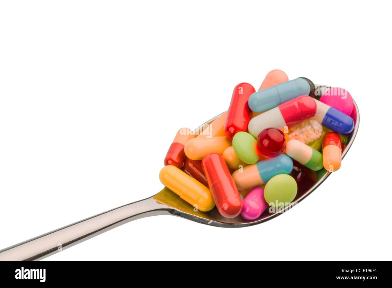 Viele bunte Tabletten auf einem Lˆffel. Symbolfoto f'r Tablettensucht und Miflbrauch von Medikamenten. Immagini Stock