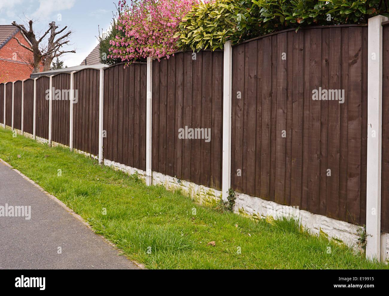 Chiudere board di pannelli di recinzione con pali di calcestruzzo dipinte recentemente con creosoto Immagini Stock