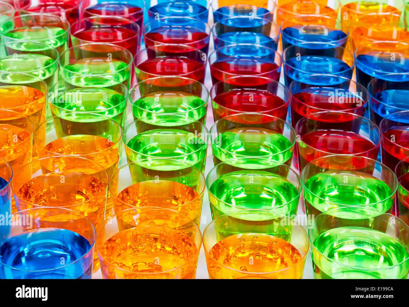 Varie bevande scatti in bicchierini creando multi bevande colorate sullo sfondo del settore Immagini Stock