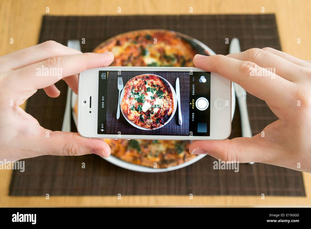 Prendere una foto di buongustai di pizza con il bianco Apple iPhone 5 Fotocamera Immagini Stock