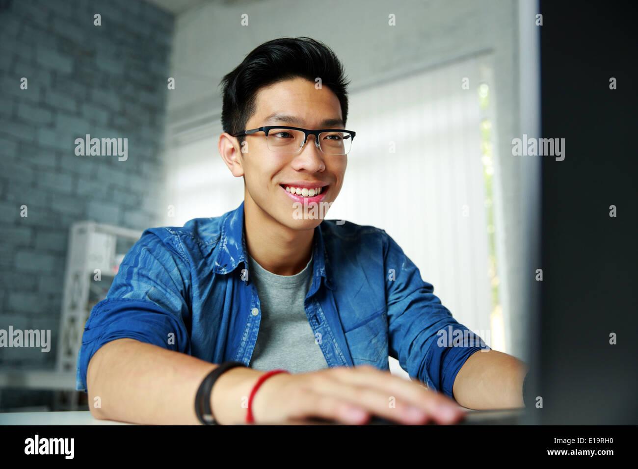 Felice giovane uomo asiatico lavorando in ufficio Immagini Stock