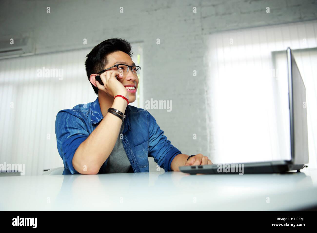 Felice asian uomo seduto al suo posto di lavoro in ufficio e parlare al telefono Immagini Stock