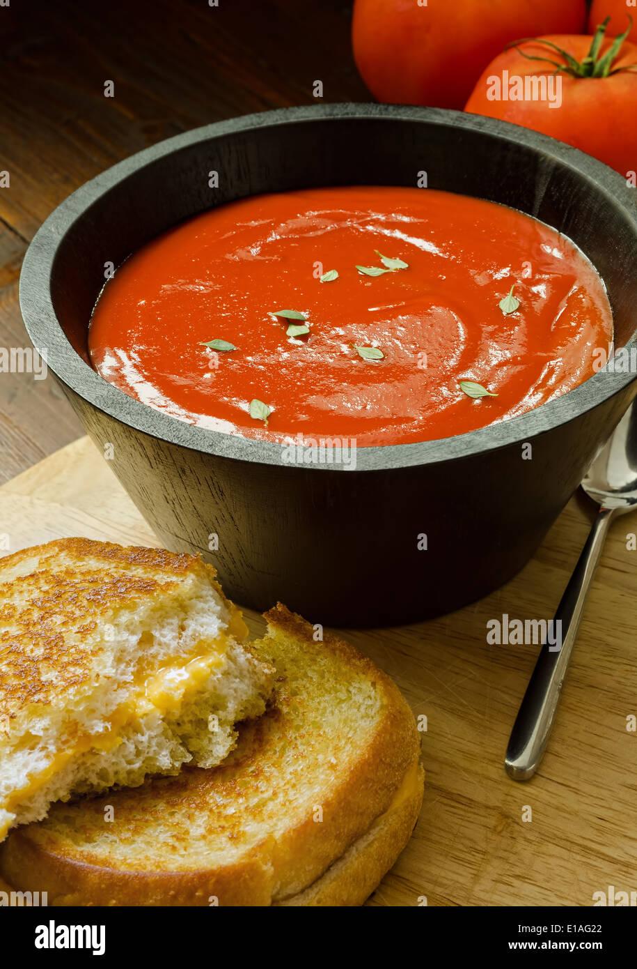 Una tazza abbondante di fatto in casa zuppa di pomodoro e formaggio alla griglia sandwich. Foto Stock