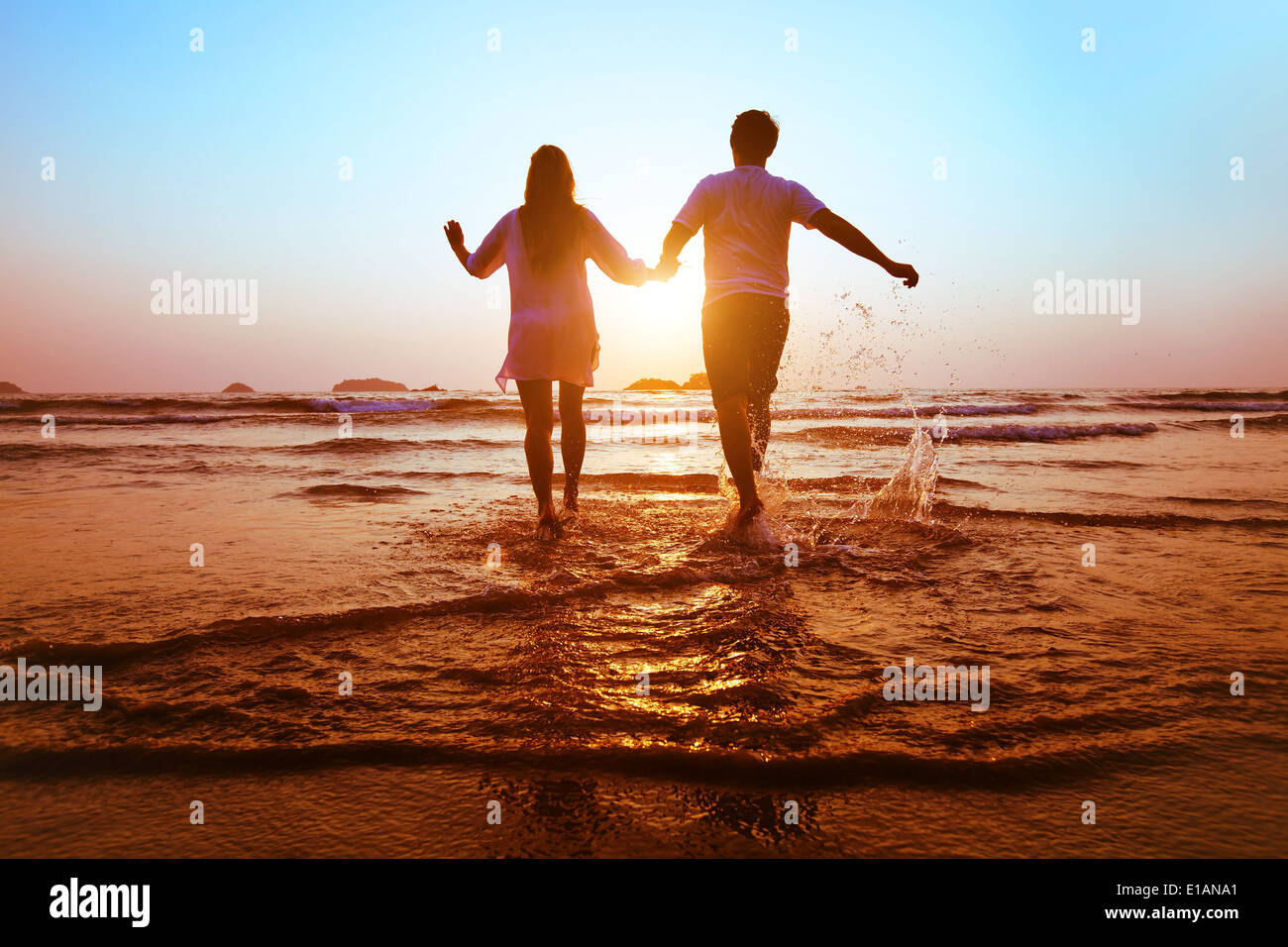 Giovane coppia felice in esecuzione al mare sulla spiaggia al tramonto Immagini Stock