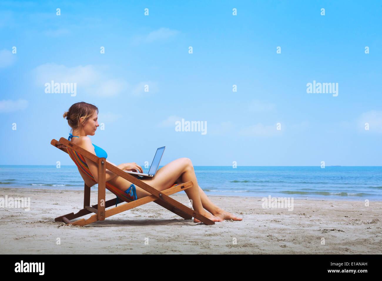 Donna in bikini seduta con il computer portatile sulla spiaggia Immagini Stock