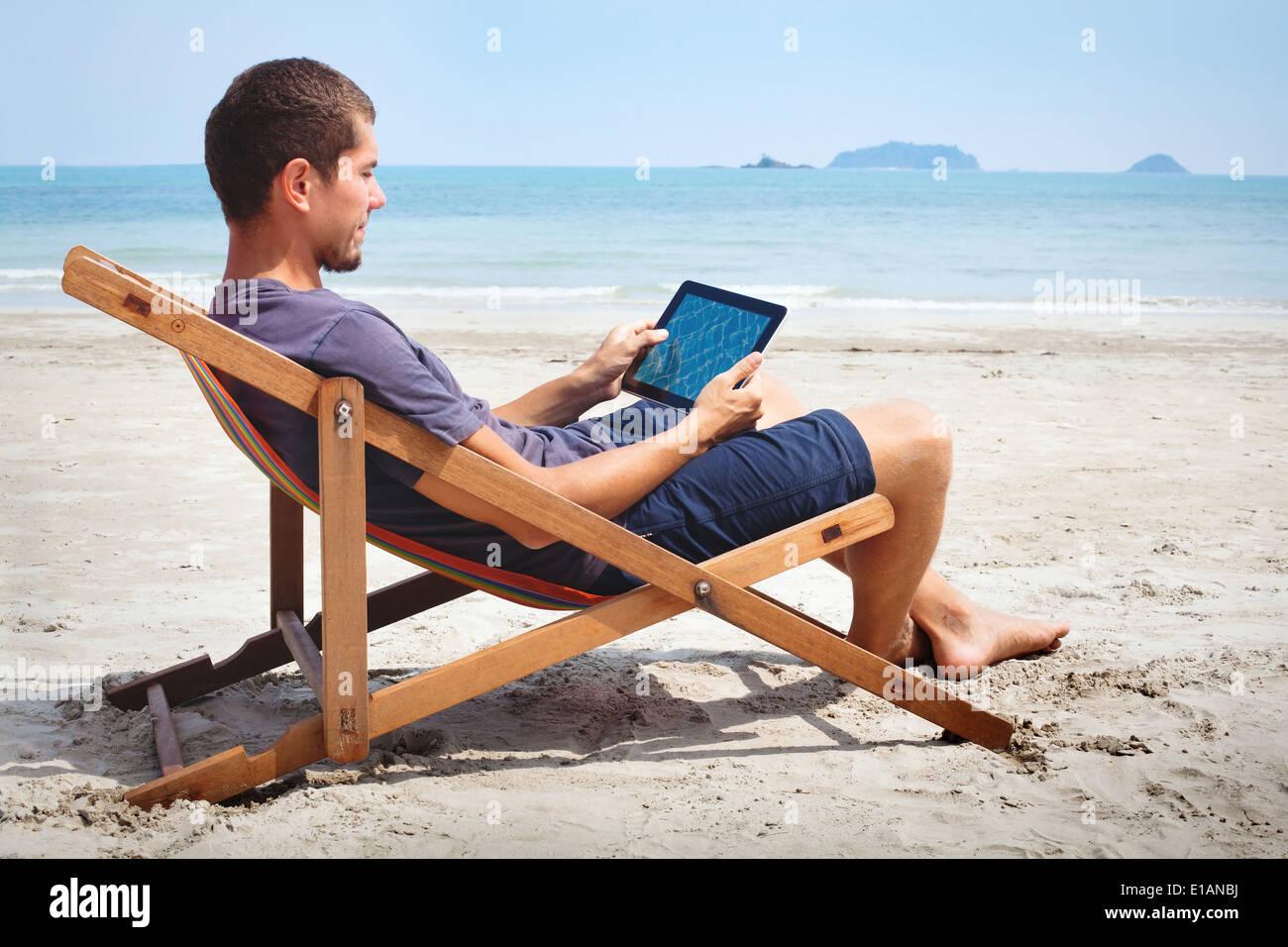 Business man lavora con la compressa sulla spiaggia Immagini Stock