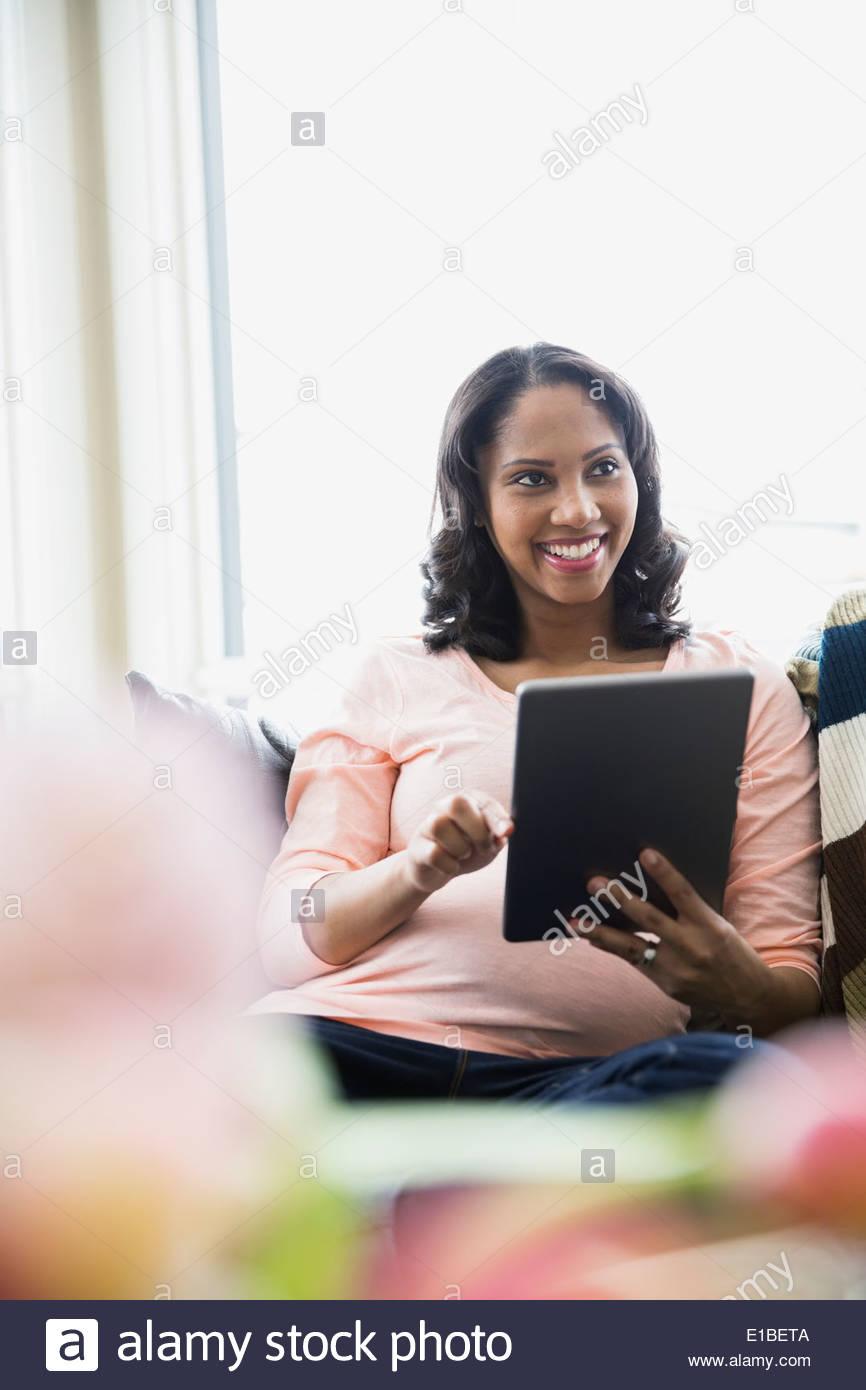 Donna incinta con tavoletta digitale in salotto Immagini Stock