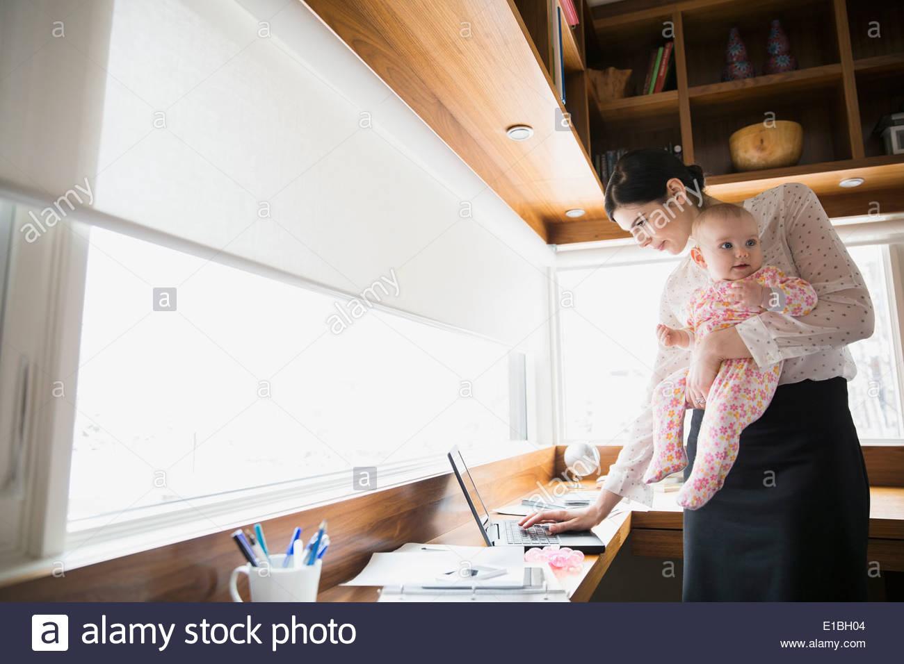 Azienda madre e bambino utilizzando computer portatile in ufficio Immagini Stock