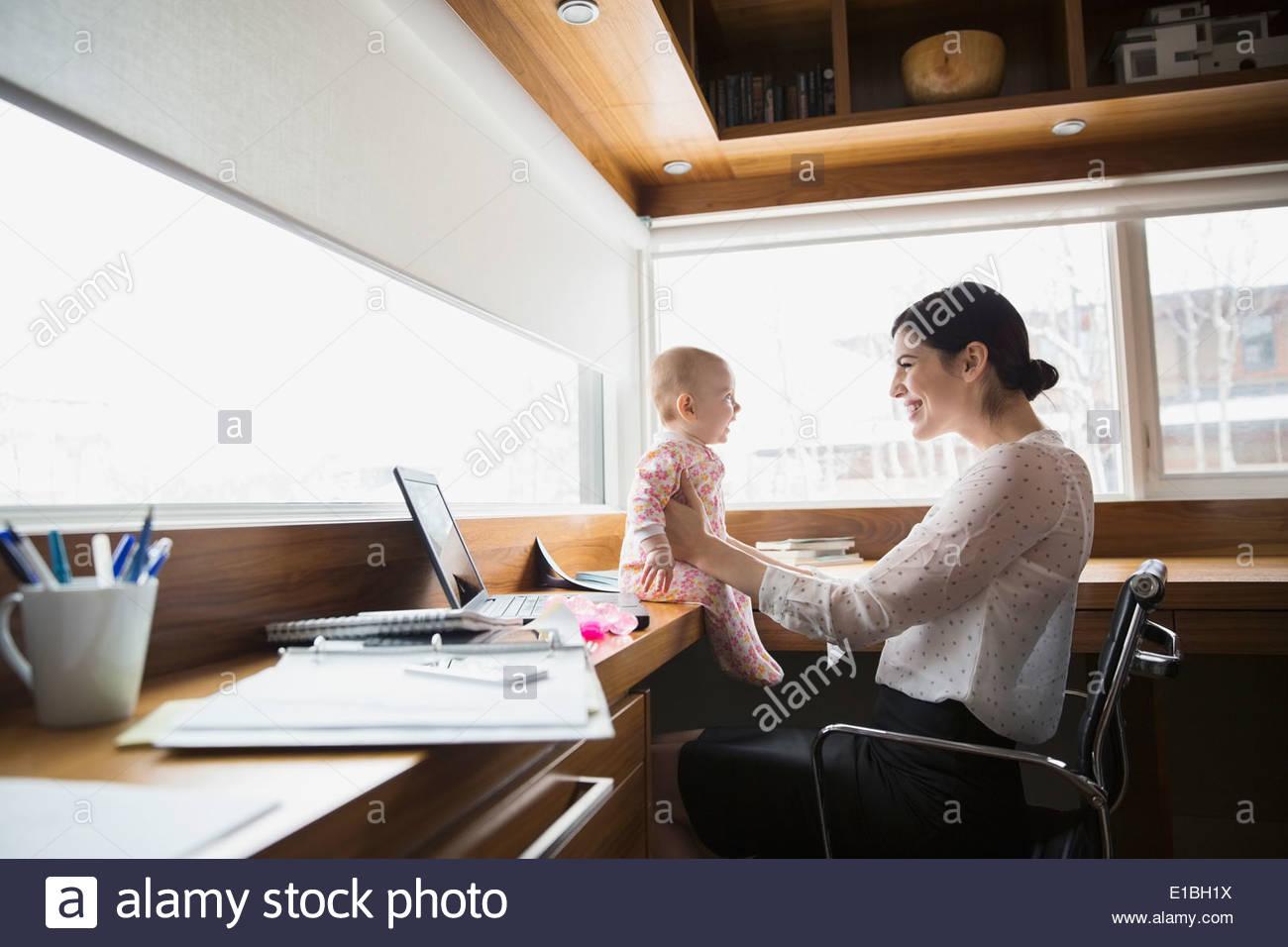 La madre e il bambino al computer portatile in ufficio in casa Immagini Stock
