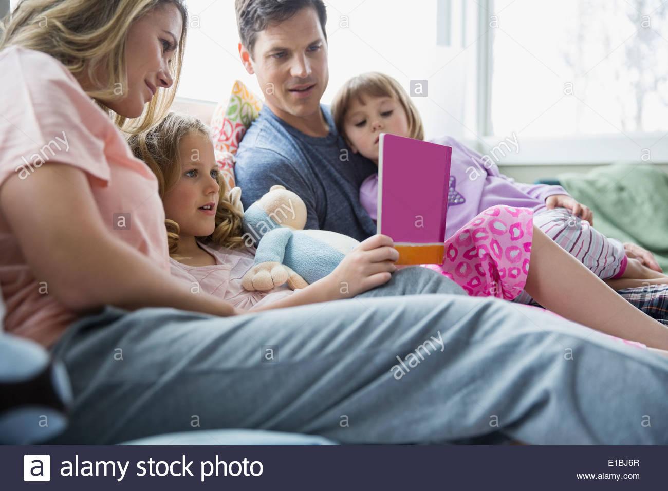 Famiglia libro di lettura sul letto Immagini Stock