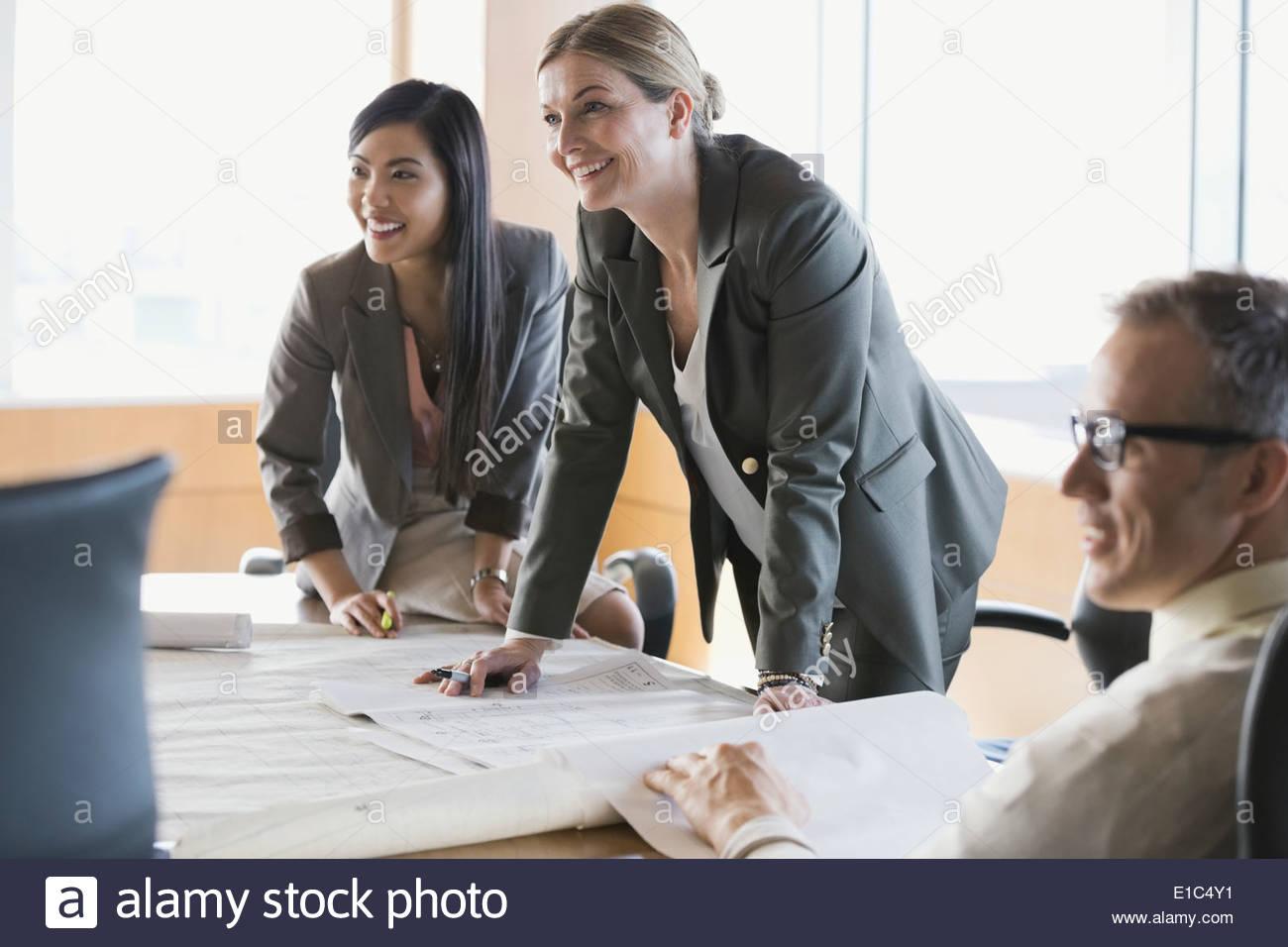 La gente di affari rivedendo blueprint in sala conferenze Immagini Stock