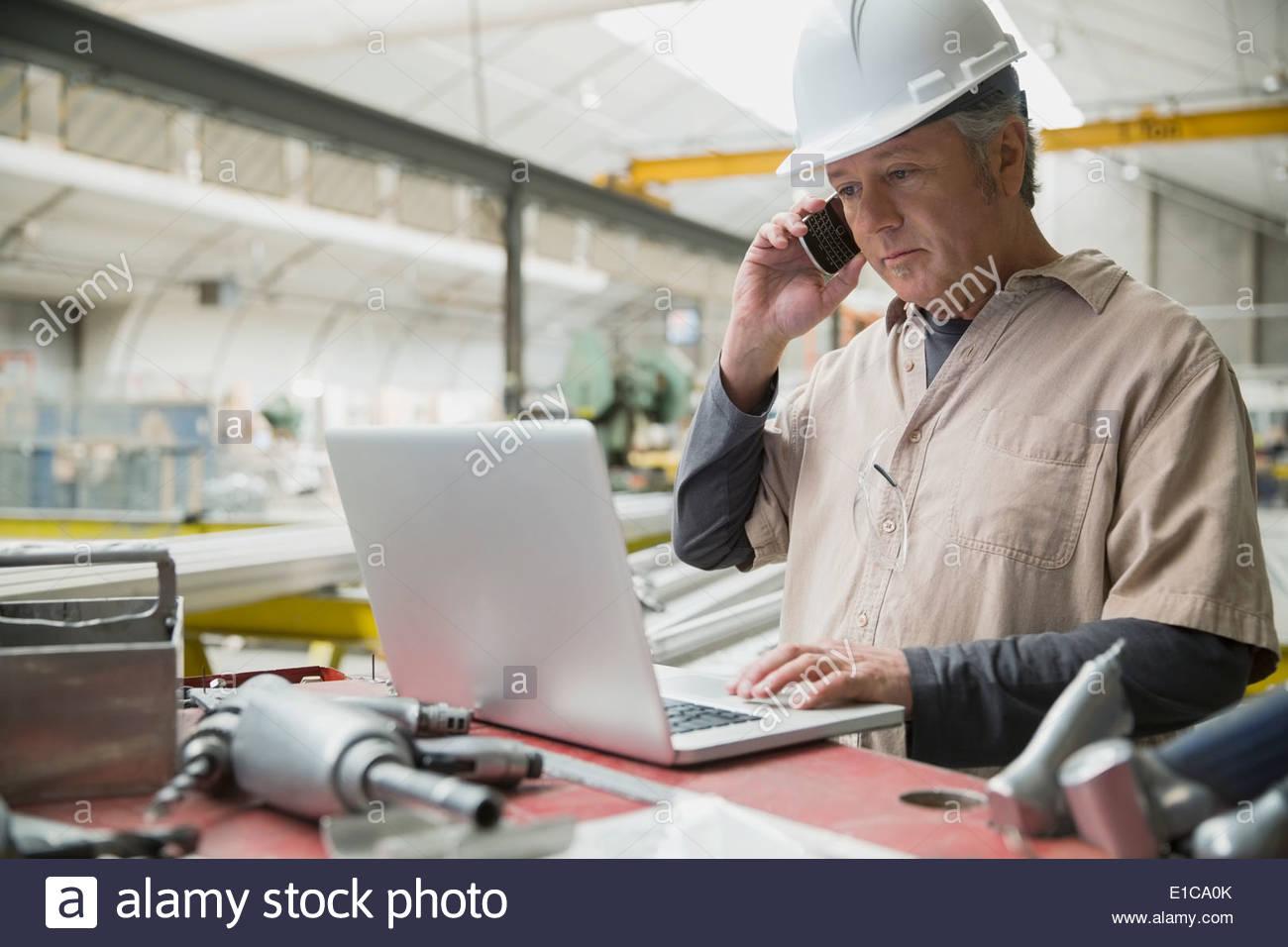 Lavoratore a laptop in impianto di produzione Immagini Stock
