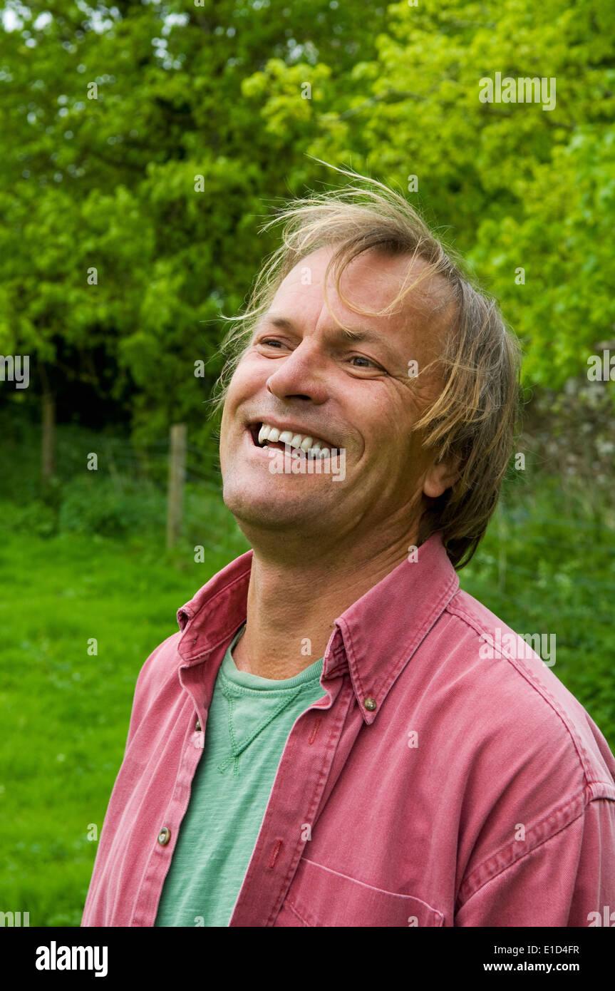 Un uomo maturo in abiti casual con capelli biondi, sorridente largamente. Foto Stock