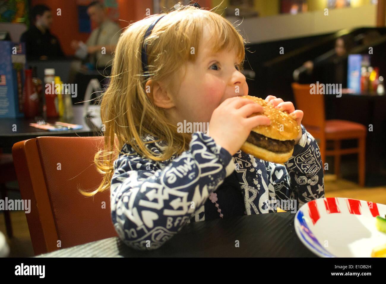 Quattro 4 anno vecchia ragazza nel ristorante mangiare formaggio hamburger Immagini Stock