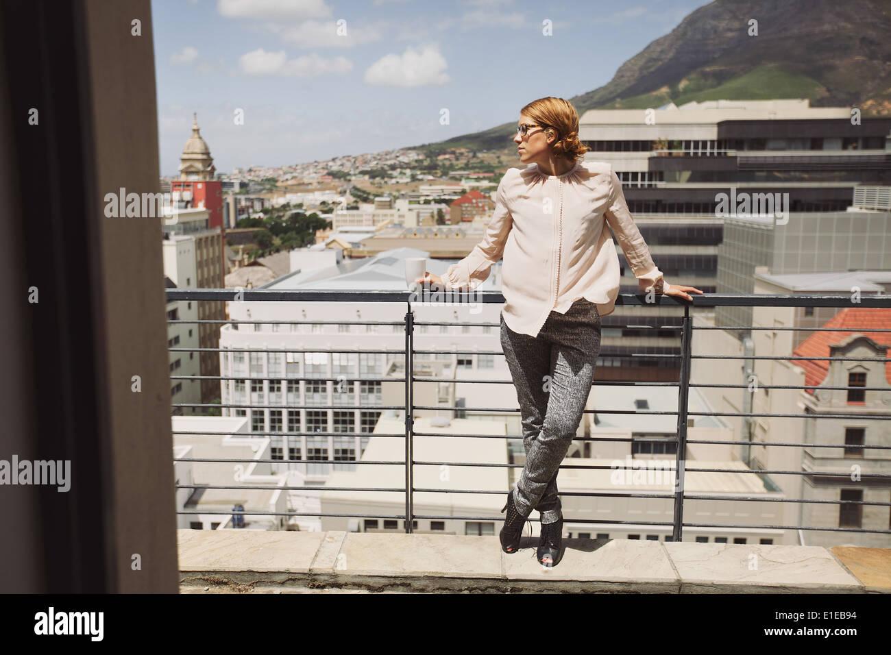 Bella giovane donna in piedi su un balcone che guarda lontano con una tazza di caffè. Caucasian modello femminile in posa su di un terrazzo. Immagini Stock