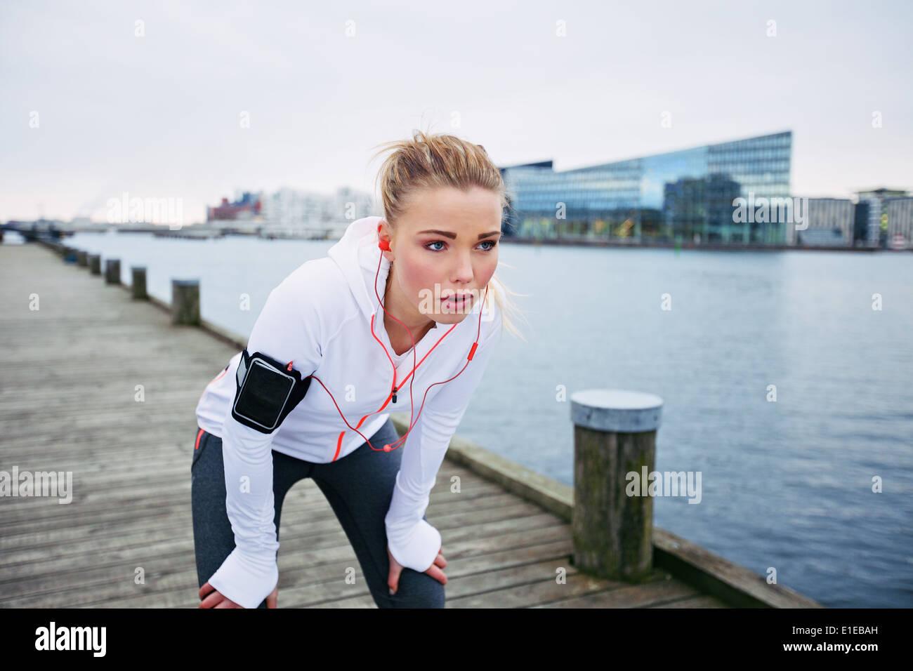 Giovani femmine runner fermandosi per un riposo mentre fuori su una corsa lungo il fiume. Donna Fitness prendendo una pausa dalla sessione di formazione. Immagini Stock