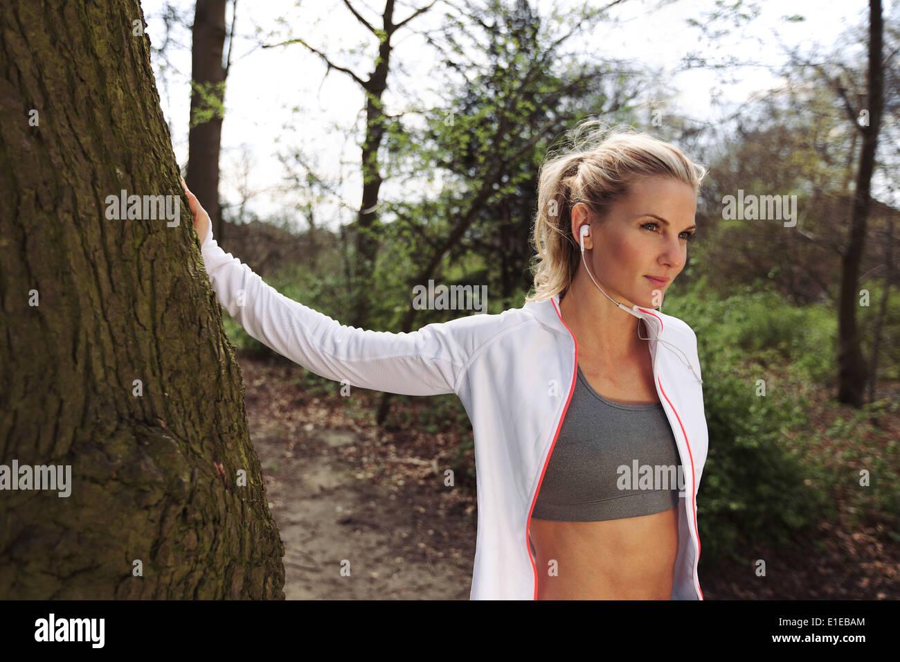 Montare femmina prendendo una pausa dopo aver eseguito sul sentiero forestale. Piuttosto giovane donna che indossa le cuffie elenco per musica e guardando lontano Immagini Stock