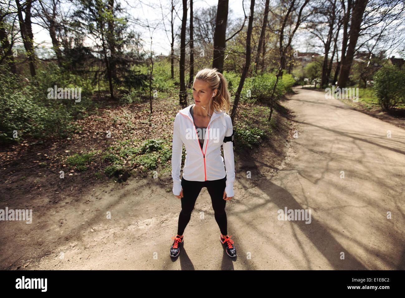 Giovane donna in esercizio abbigliamento in piedi su un sentiero forestale che guarda lontano. Femmina fitness all'aperto sulle sessioni di formazione. Immagini Stock