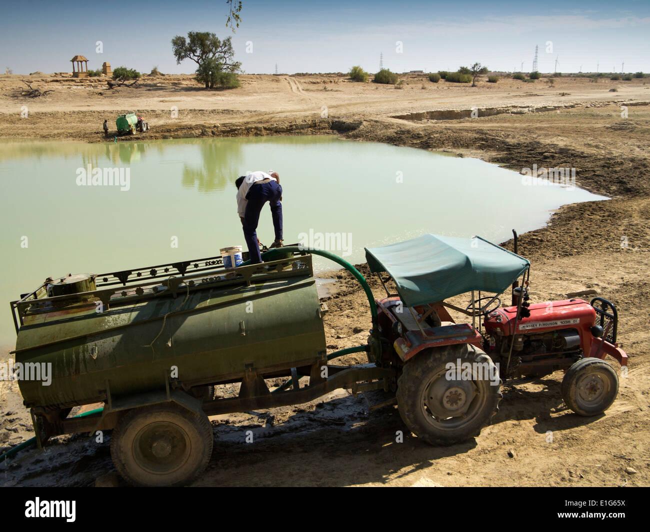 India Rajasthan, Jaisalmer, deserto di Thar, gli agricoltori il riempimento di trattore tirato il serbatoio con acqua di irrigazione al lago Immagini Stock