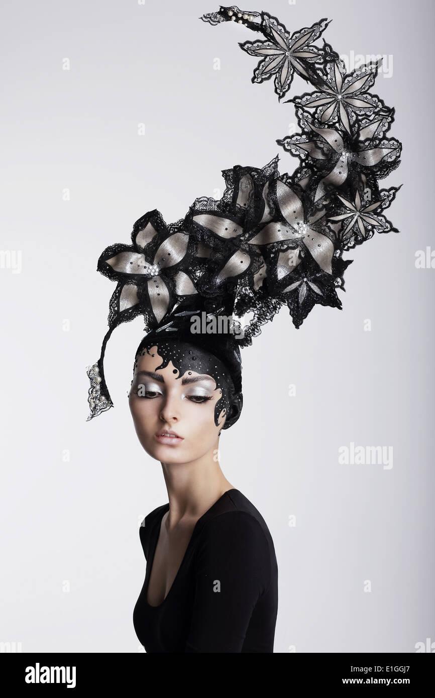 La fantasia. Il surrealismo. Incredibile donna nel quartiere alla moda di copricapi con fiori Immagini Stock