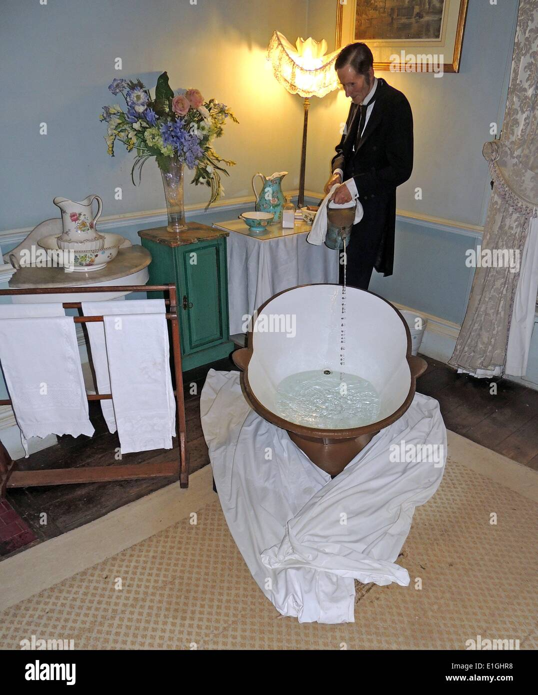 Bagno in stile vittoriano con maggiordomo versando acqua calda a piastrelle bagno en-suite. Immagini Stock
