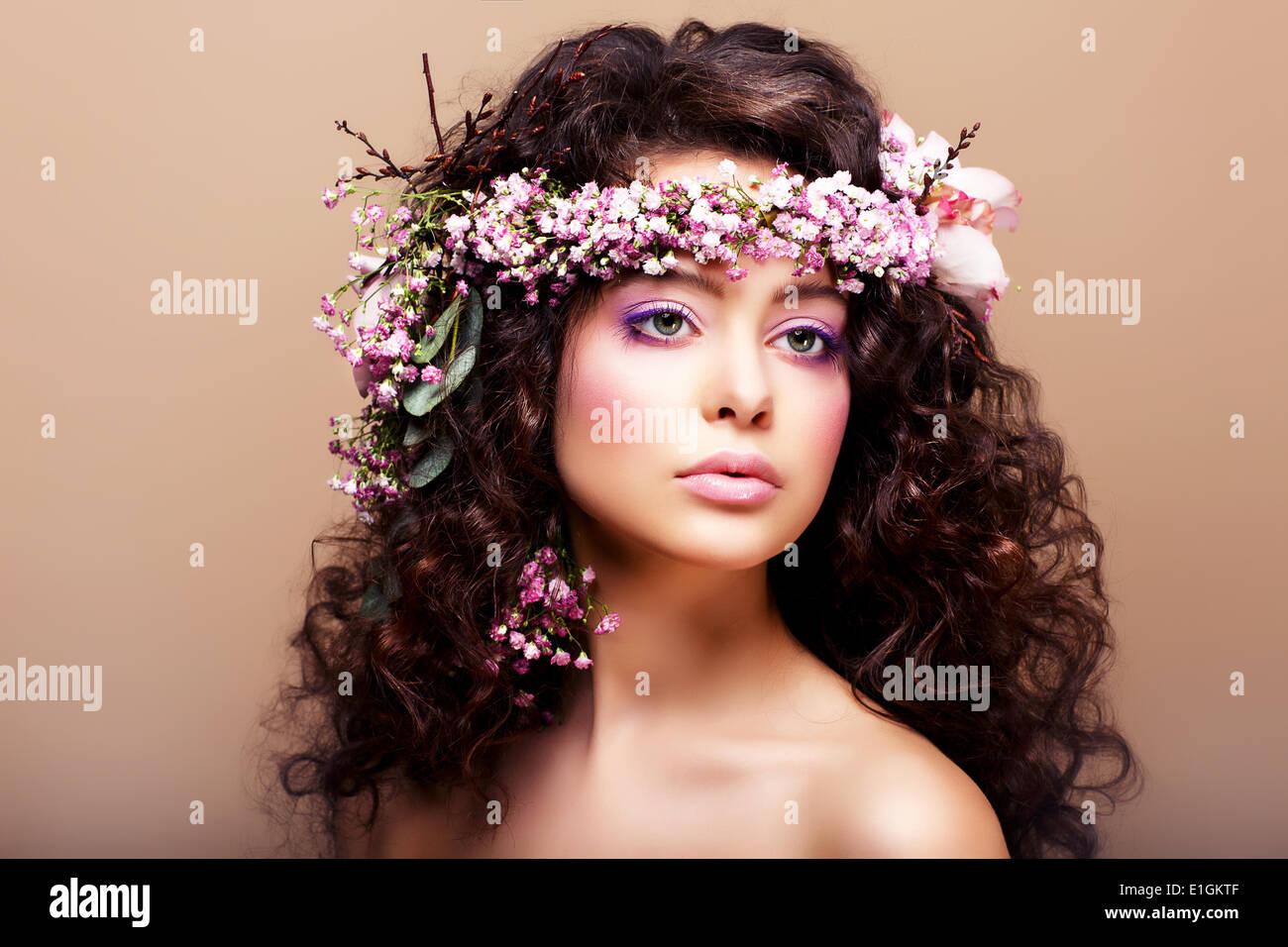 Rigogliosa. La femminilità. Modello di moda con la classica ghirlanda di fiori Immagini Stock