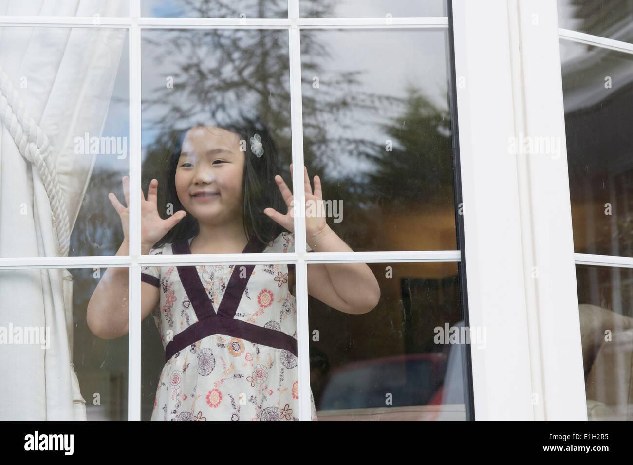 Ragazza giovane guardando fuori dalla stanza di seduta finestra Immagini Stock