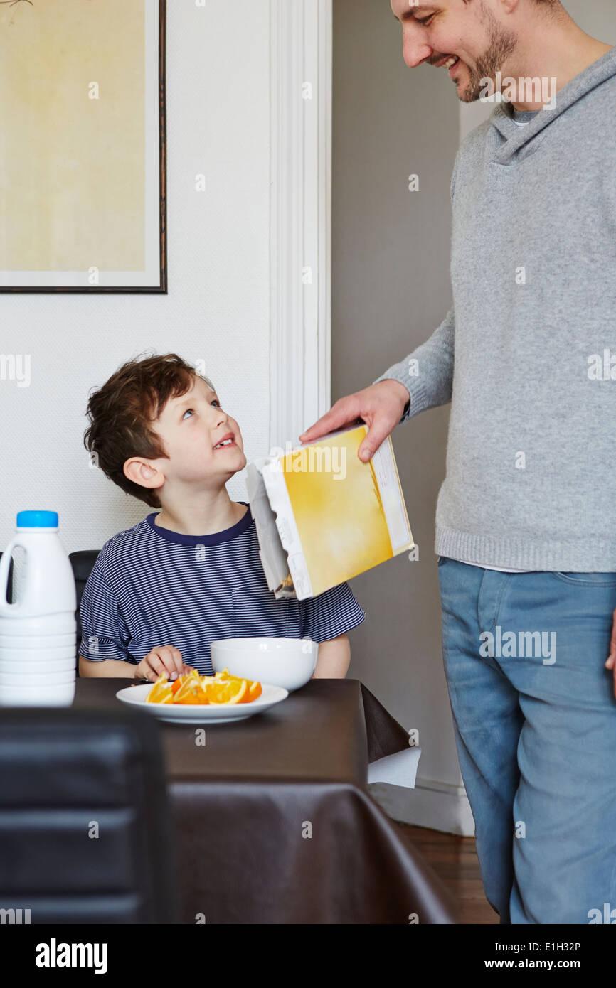 Padre versando cereale in figlio la vaschetta Immagini Stock