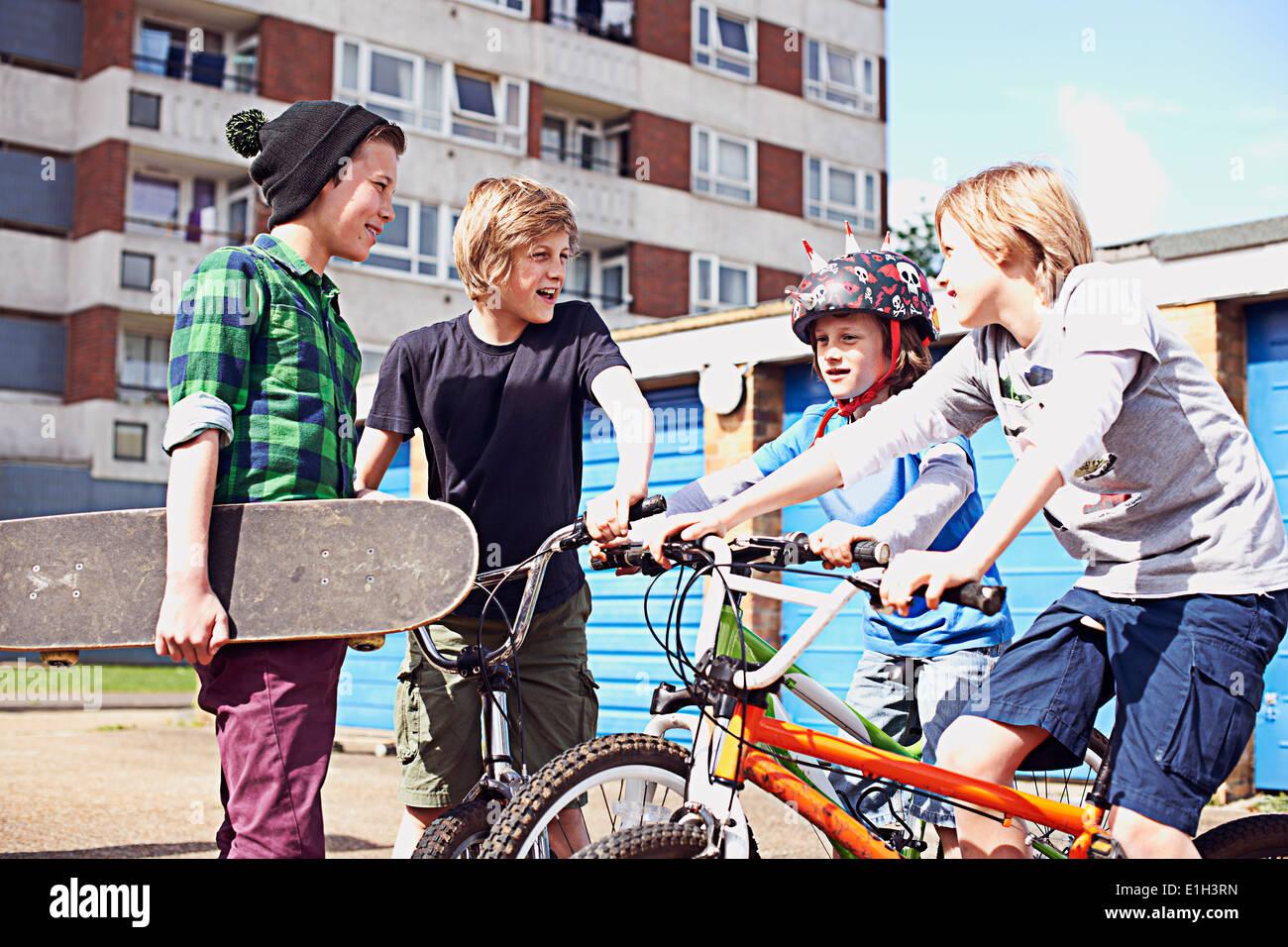 Un gruppo di ragazzi a parlare con le biciclette e skateboard Foto Stock