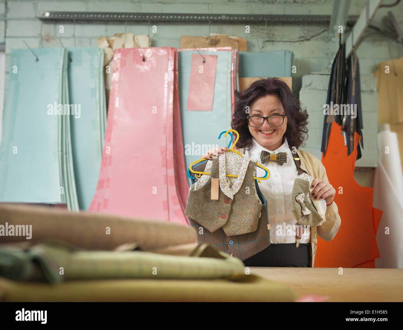 Designer di moda con bambini usura nella fabbrica di abbigliamento, ritratto Immagini Stock
