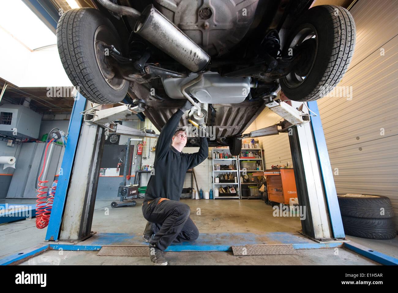 Un meccanico è controllo dello scarico di una vettura che è sollevata in una riparazione alla stazione di servizio. Immagini Stock