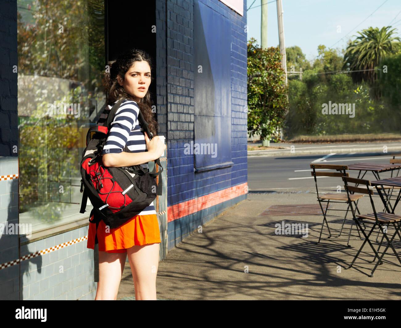 Giovane donna sulla strada guardando sopra la sua spalla Immagini Stock