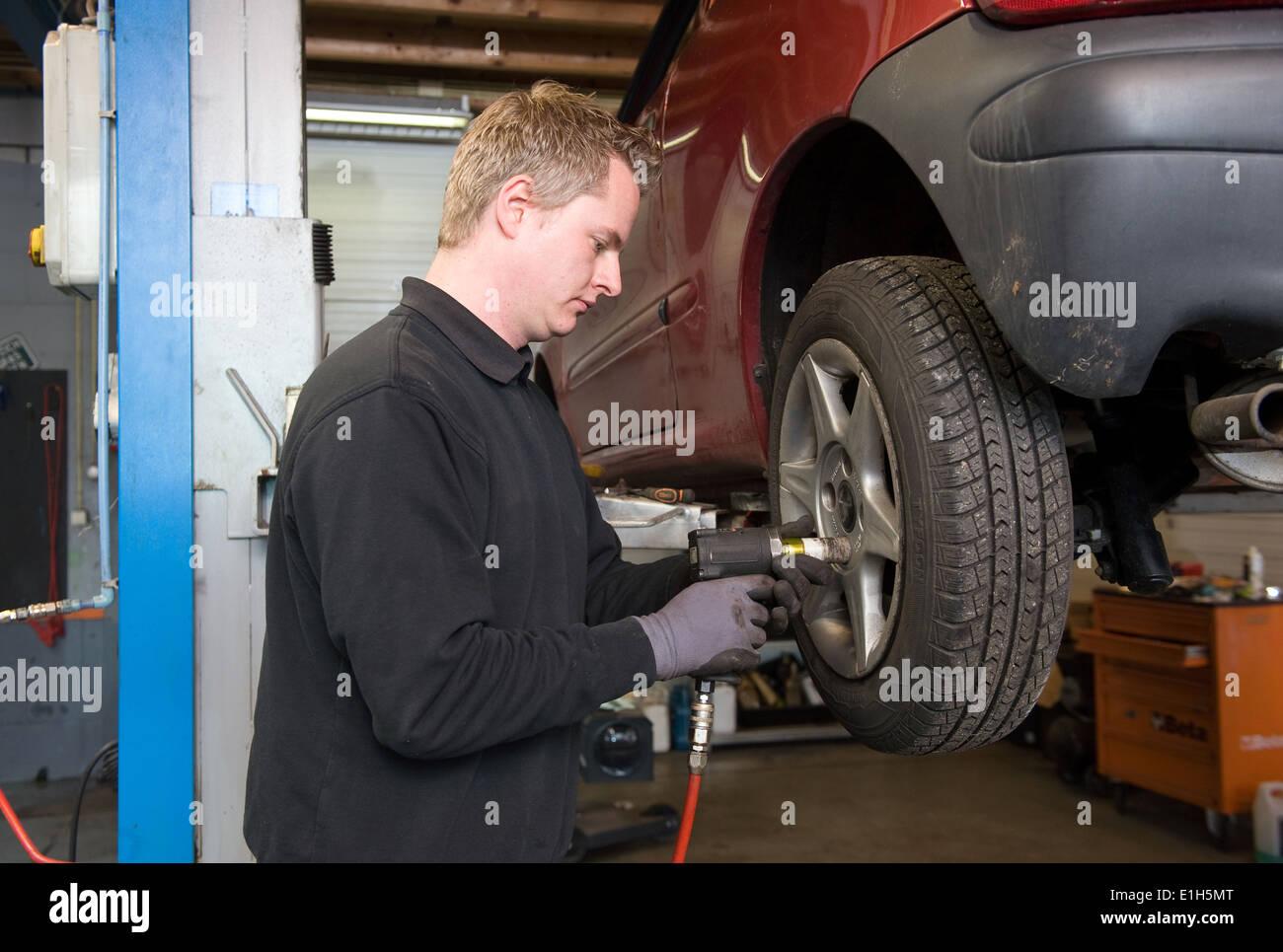Un meccanico sta lavorando sulla ruota di una vettura che è sollevata in una riparazione alla stazione di servizio. Immagini Stock