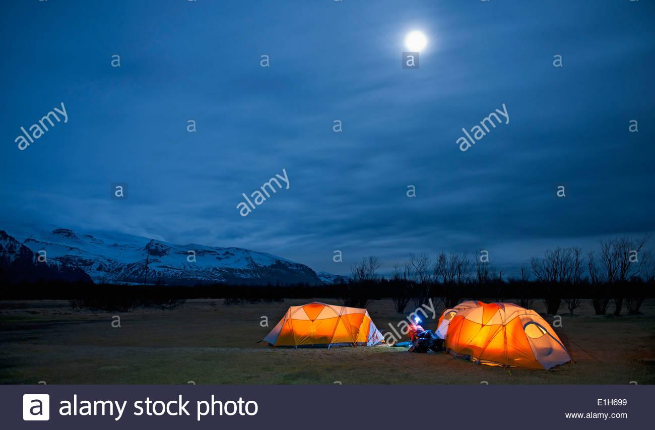 Donna matura seduto fuori tenda di notte, Skaftafell, Vatnajokull National Park, Islanda Immagini Stock