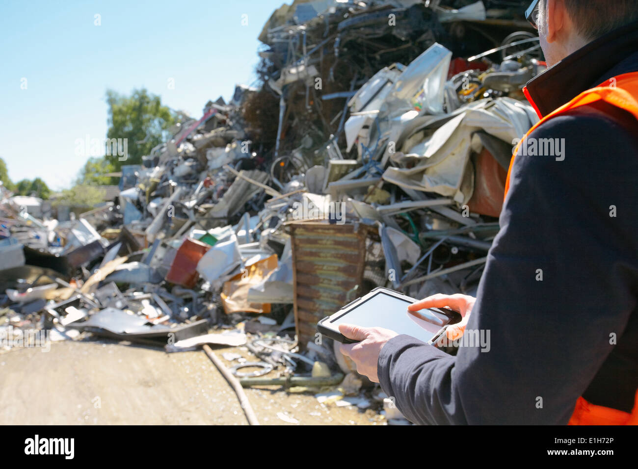 Caposquadra con tavoletta digitale a rottami di metallo impianto di riciclaggio Immagini Stock