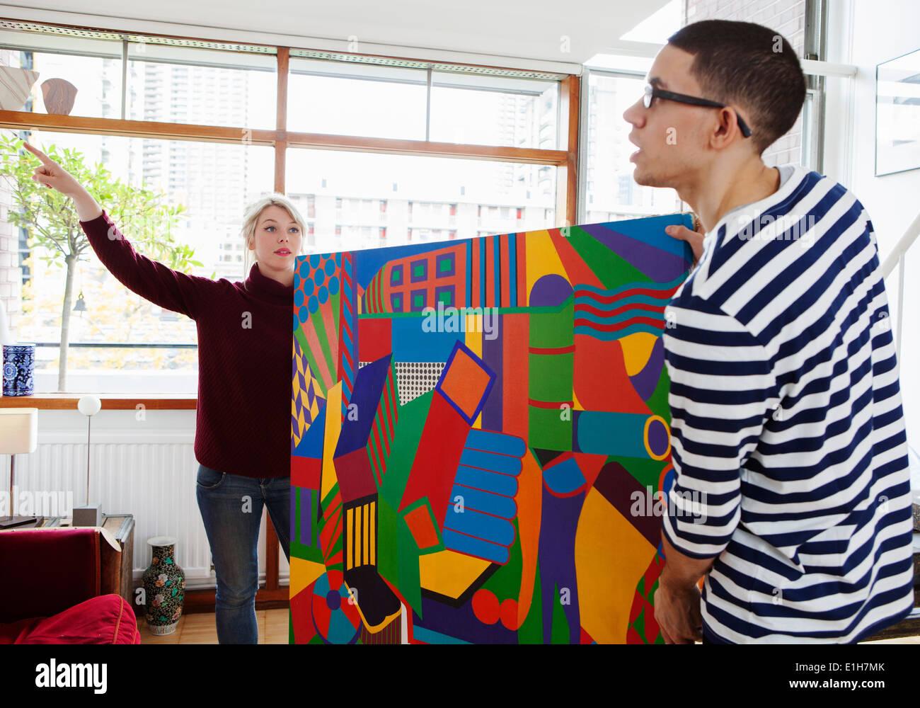Coppia giovane mettendo la pittura in salotto Immagini Stock