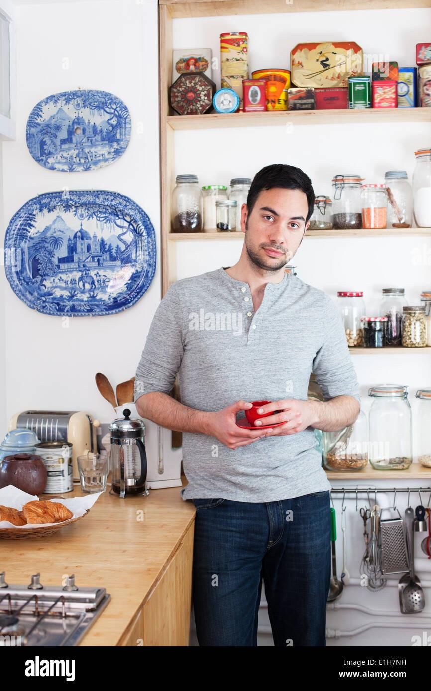Metà uomo adulto in piedi in cucina azienda tazza da caffè Immagini Stock